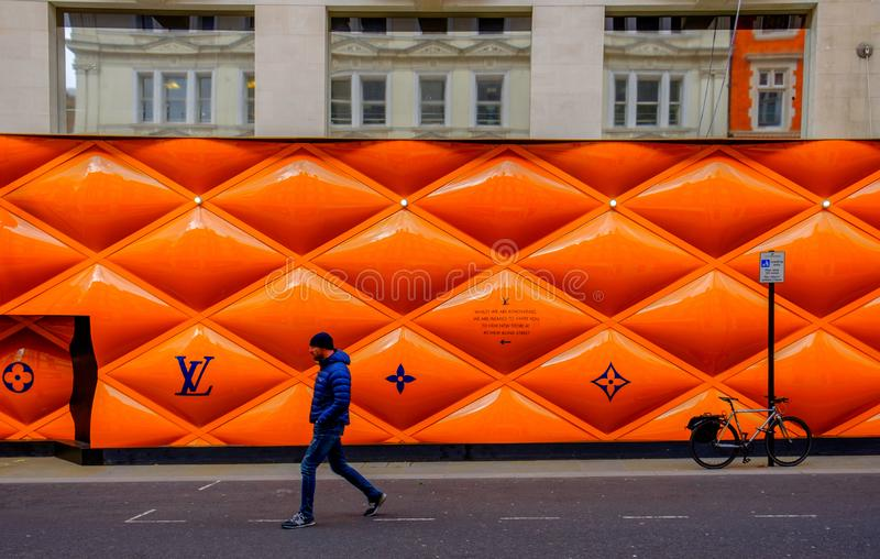 London-LV Building Site Fence Panels. London, U.K, March 2019, man passing by building site fence panel for a Louis Vuitton shop in the Mayfair area stock photography