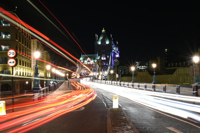 London, majestätisk och historisk tornbro för UK, på natten, med ljusa slingor av bussar och bilar som skapas med det långa expon royaltyfria foton