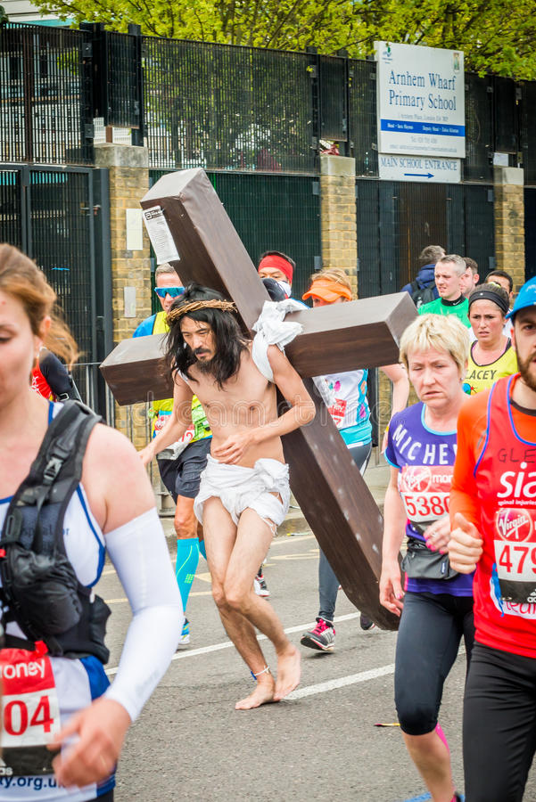 London Marathon 2016. London, United Kingdom - April 24, 2016: London Marathon 2016. Runners in great costumes. Barefoot runner as Jesus with a cross on his back stock photo