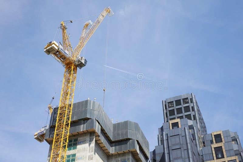 LONDON -, MAY 2017: Kran och moderna byggnader under konstruktion mot blå himmel, i staden av London arkivbilder
