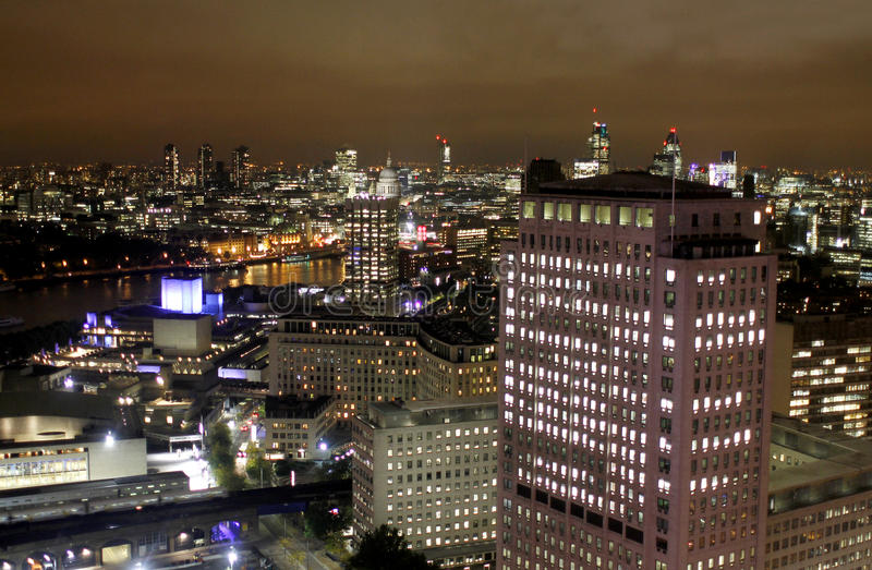 London night scene, Canary Wharf office buildings. London UK night scene of business district Canary Wharf with illuminated office buildings aerial view stock photography
