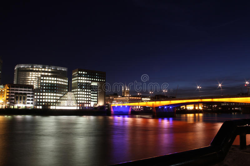 London nightscape with bridge. A view of an illuminated bridge and modern commercial waterfront buildings on the banks of the River Thames in London at night royalty free stock photography