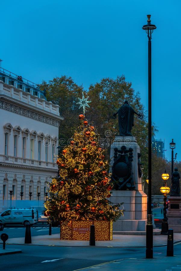 Christmas tree at Waterloo Place, London. LONDON - NOVEMBER 21, 2019: Christmas tree at Waterloo Place opposite the Sofitel Hotel St James`s is decorated in gold royalty free stock photo