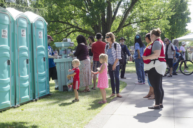 London Ontario, Canada - July 16, 2016: Children waiting with th. Eir mom for street bio-toilet in the park Victoria Park during the country festival as royalty free stock photography