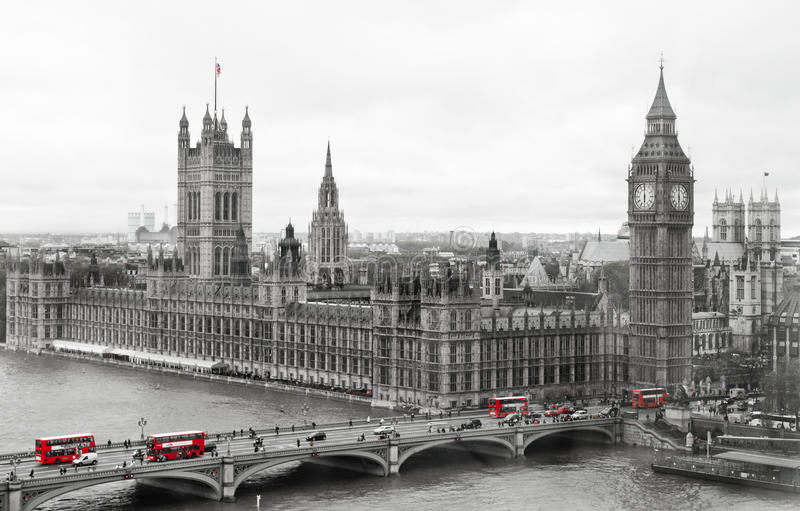 London Parliament and Big Ben. Big Ben and the Houses of Parliament in black and white in contrast with the red buses that run on the bridge crossing the River stock photo