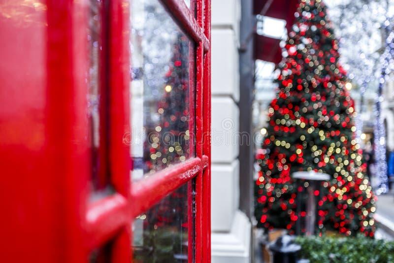London röd telefonask och julgran royaltyfri bild
