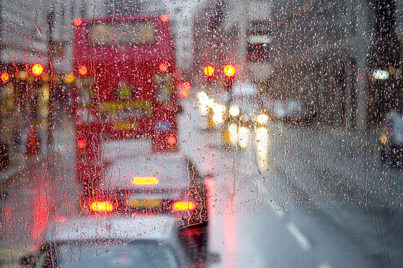 London rain view to red bus through rain-specked window royalty free stock photo