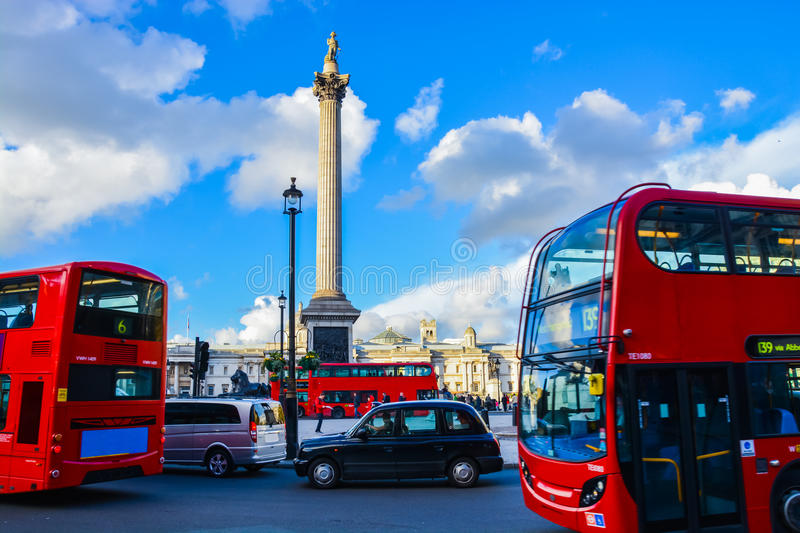 London Red buses in front of Trafalgar Square - London. Traffic travelling around Trafalgar Square Nov 2014 - central London stock photos