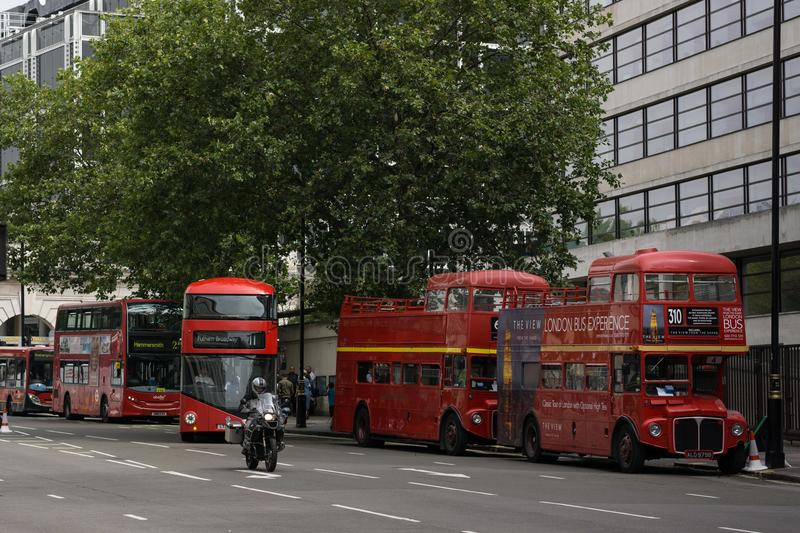 London red buses of old and new style next to eachother. Several London Transport red buses next to each other in the street in central London. Two are the old royalty free stock photos