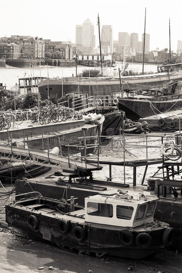 London's Docks in Black and White. London, UK - May 4th, 2015: boats piled in the shallow waters of the River Thames in London. Processed in B&W stock image