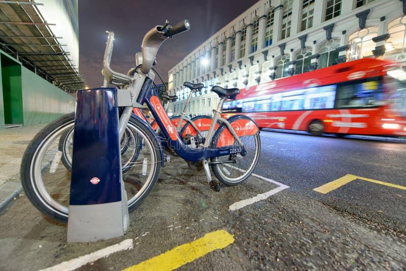 LONDON - 25. SEPTEMBER 2016: Roter Bus und reantal Fahrradstation an lizenzfreie stockbilder