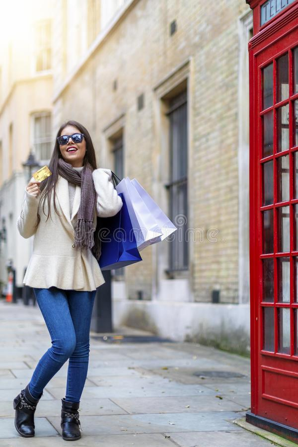 London shopping concept with an attractive fashion girl. London shopping concept: attractive fashion girl with many shopping bags and a credit card in her hand stock images