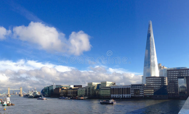 London skyline while crossing London Bridge with The Shard and Tower Bridge Mar-16-13 reflections clouds skyscrapers river Thames royalty free stock photography