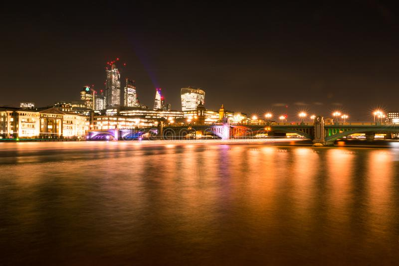 London Skyline at Night with Thames River, Bridges, City Buildings and Riverboats Crossing.  royalty free stock photography