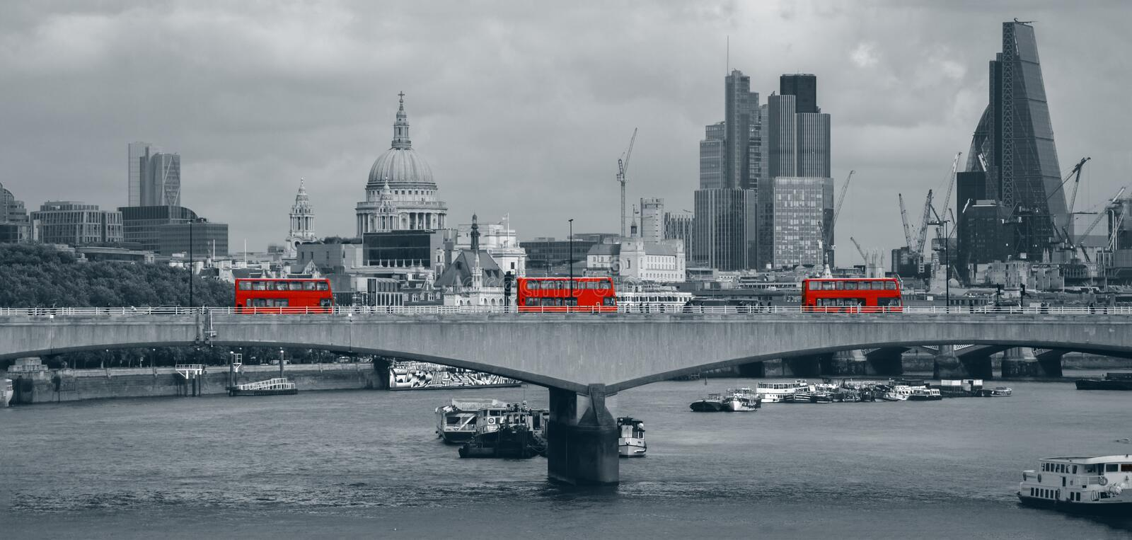 London skyline with red buses. This picture was taken looking across a bridge in London overlooking the Thames River. By pure chance three buses passed over at