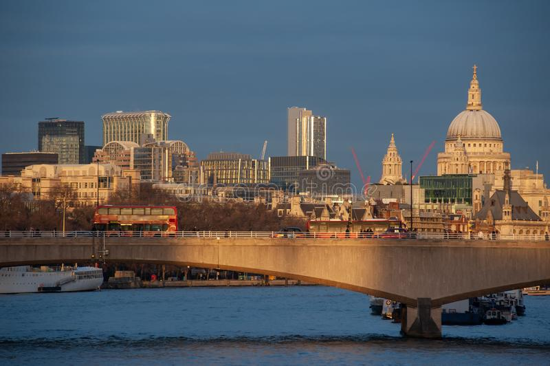 London skyline at sunset from river Thames. Waterloo Bridge and St Paul`s Cathedral. London skyline at sunset from river Thames. People and buses crossing stock image