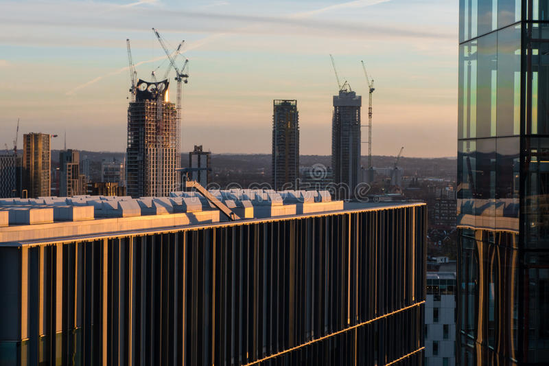 London skyline at sunset with skyscraper construction cranes. Details of office and apartment buildings against London skyline in sunset with high rise building stock photo