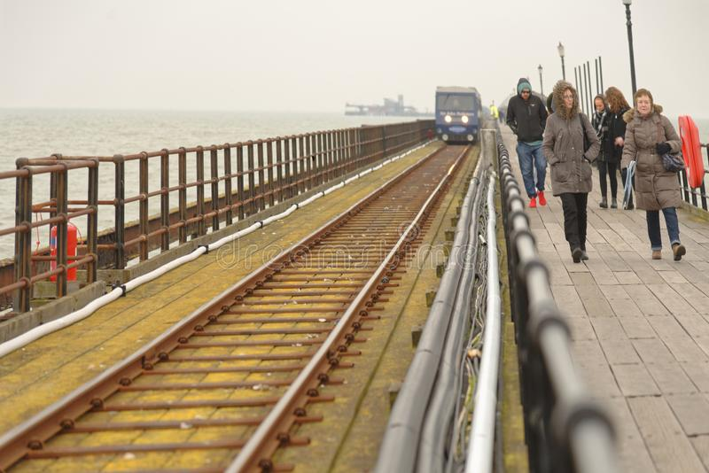 London, Southend: pier deck and railway. People walking along southend Pier, Essex on a freezing cold day in england, uk royalty free stock image
