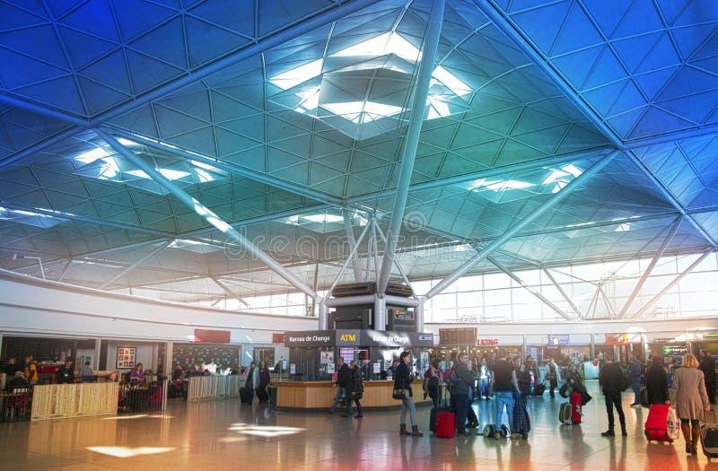 LONDON STANSTED FLYGPLATS, UK - MARS 23, 2014: Passagerare i flygplatsavvikelsearian och att vänta av informationsskrivbordet som royaltyfri foto