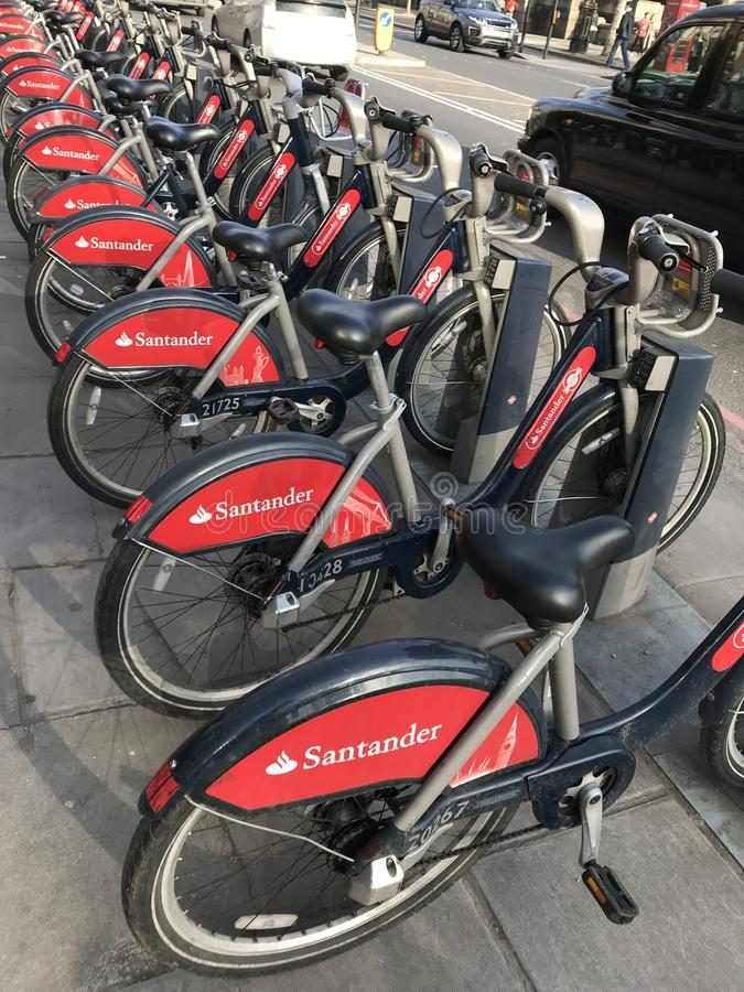 London Red `Boris` Bikes / Bicyicles with black cab/taxi. London street with a row red bicycles and black taxi on a road. Environmentally friendly way of stock images