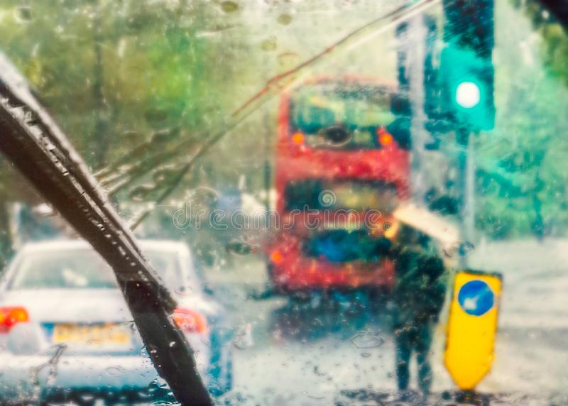 London street scene abstracted by rain on a car windscreen on a rainy day. A red bus can be seen and a man holding cardboard above. His head for shelter by a royalty free stock image