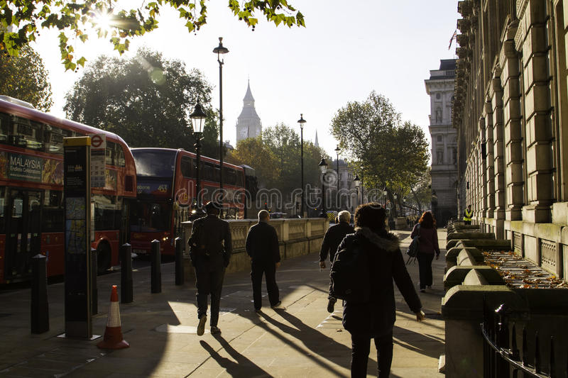 London streets in autumn. With city landmarks. In this photo Big Ben is visible in the far distance, with two red buses on the left side. People are commuting royalty free stock photos