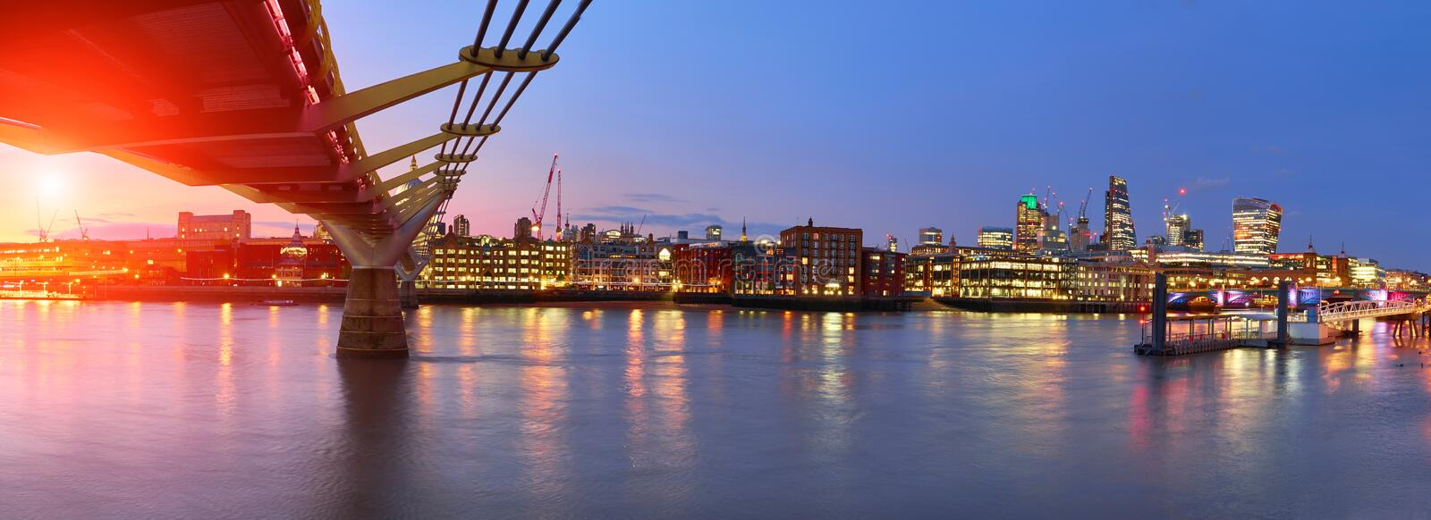 London at sunset, Millennium bridge leading towards illuminated St. Paul cathedral over Thames river. With city bathing in electric light. Panoramic toned image stock photography