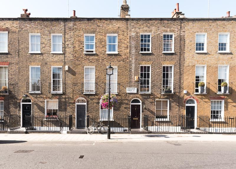 London Terrace Houses. Front facades and arched doors of historic brick London Terrace houses with tall windows and iron railing out front with a bicycle on the stock photos