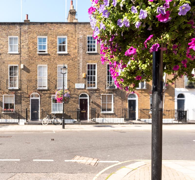 London Terrace Houses. Front facades and arched doors of historic brick London Terrace houses with tall windows and iron railing out front with a bicycle on the stock photo
