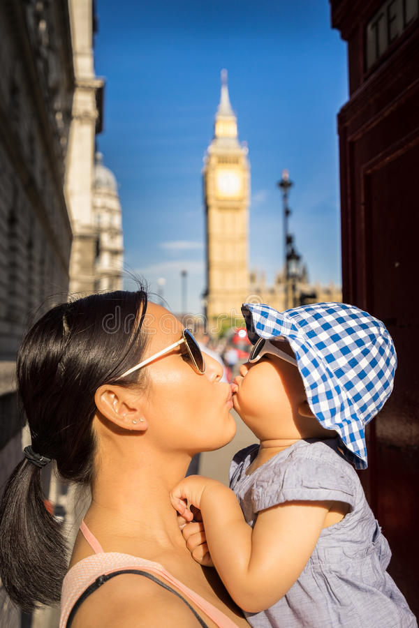 London travel Mother and Baby tourist by Big Ben. Travel tourist in london sightseeing, near Big Ben.Happy cheerful family. Mother and baby playing kissing stock photos