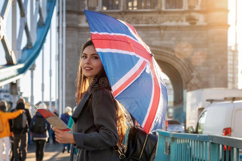 London traveler tourist with a British flag umbrella in London, UK. Attractive, young London traveler tourist with a British flag umbrella on the Tower Bridge in royalty free stock photo