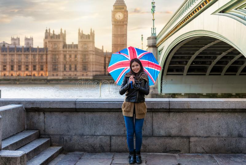 London traveler woman during a sightseeing trip. Attractive London traveler woman with a British flag umbrella stands in front of the Westminster Palace during a royalty free stock image