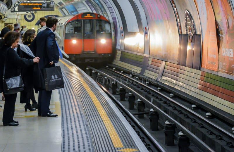 London tunnelbana - folk som väntar på ett drev royaltyfria bilder