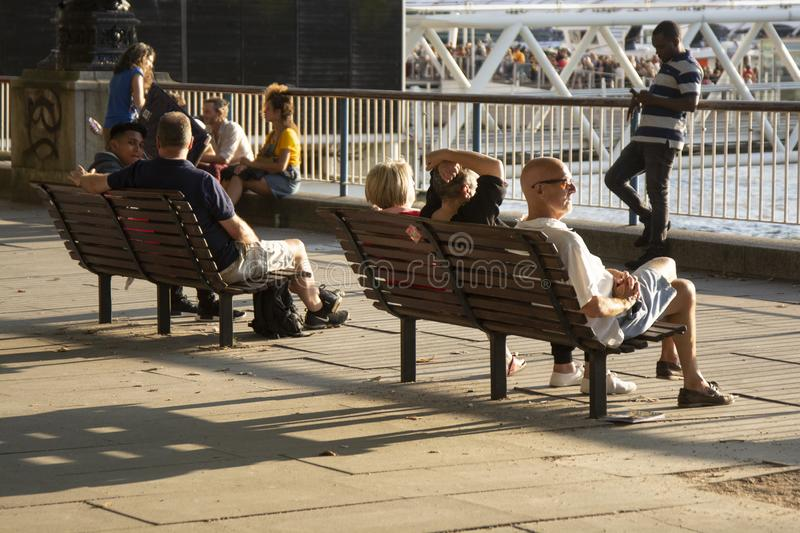 London, U.K., August 22, 2019 - Tourists sit on a Southbank bench with a view of St Paul s Cathedral and the Thames stock photos