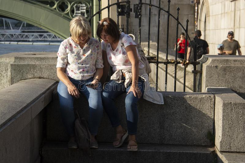 London, u.K., August 22, 2019 - two older woman taking selfies or photos traveling in London royalty free stock photography
