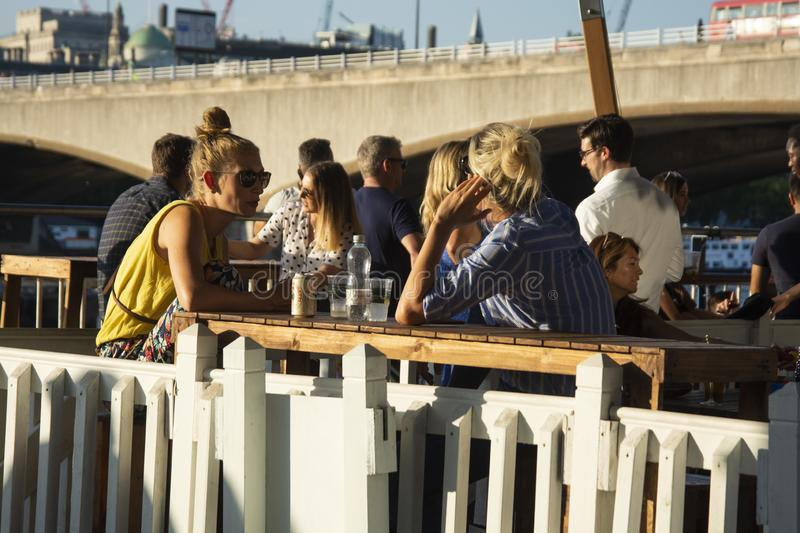 London, U.K. August 23, 2019 - Young people enjoy and relax at an outdoor cafe terrace in London, at river Thames. Wekeend time. London, U.K. August 23, 2019 stock photo