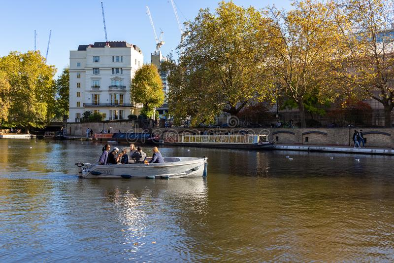 People in the boat at Regent`s Canal next to Paddington in Little Venice, London - England, UK. LONDON, UK – Oct 21, 2018: People in the boat at Regent`s royalty free stock image