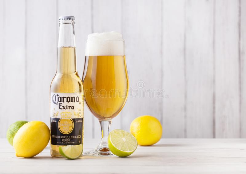LONDON, UK - APRIL 27, 2018: Bottle of Corona Extra Beer on wood. En background with fresh lemons and limes . Corona, produced by Grupo Modelo royalty free stock images