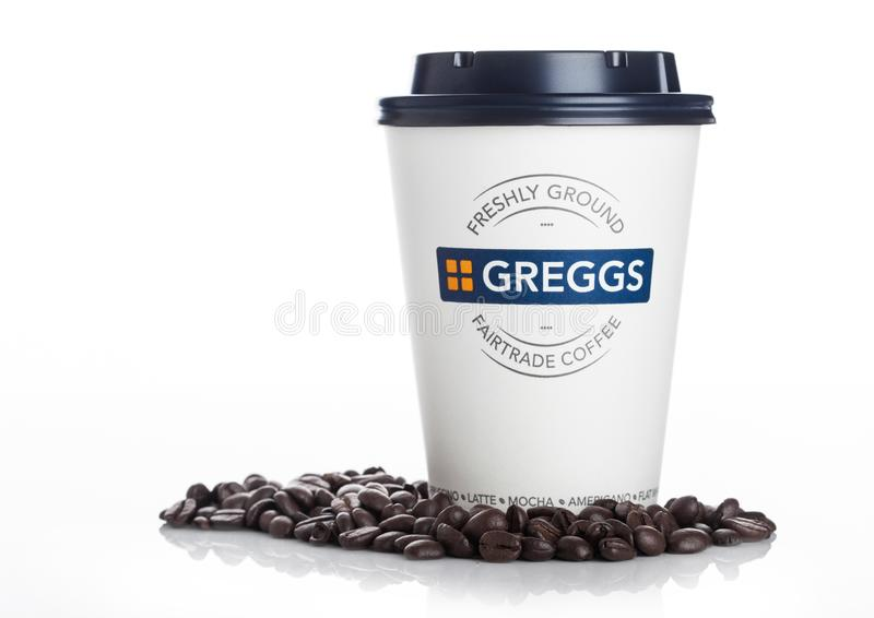 LONDON, UK - APRIL 15, 2019: Closeup of Greggs fairtrade paper coffee cup and sign with lid on white background with beans stock photo