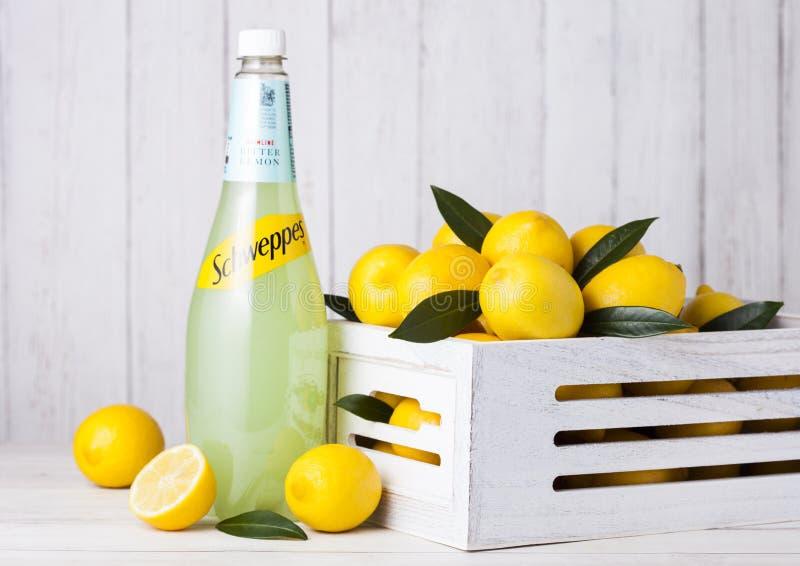 LONDON UK - APRIL 27, 2018: Flaska av drinken för Schweppes citronjuicebrusande på träbakgrund med nya citroner arkivbilder