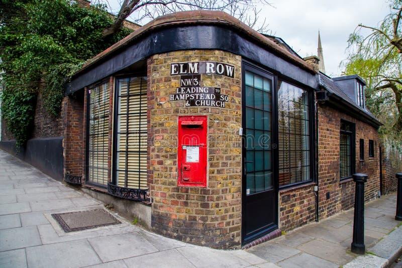 LONDON UK - April, 13: Röd postbox med det belade med tegel gatatecknet, London royaltyfri fotografi