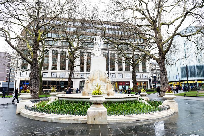 Marble statue of William Shakespeare at Leicester Square Garden in London, United Kingdom. London, UK - April 2018: The Shakespeare fountain and marble statue of stock photos