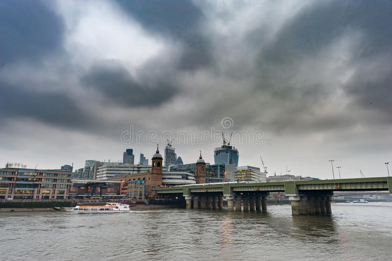 LONDON, UK - APRIL 9, 2013: Thames River with Ferry and Business Center in Background. Cloudy Day. royalty free stock photography