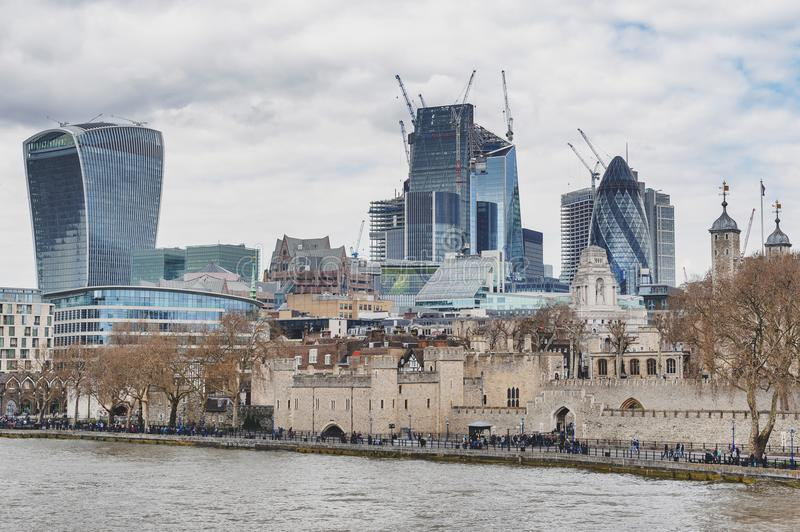 Tower of London by the River Thames with skyscrapers and buildings constructed in modern architectural style, England. London, UK - April 2018: Tower of London royalty free stock image