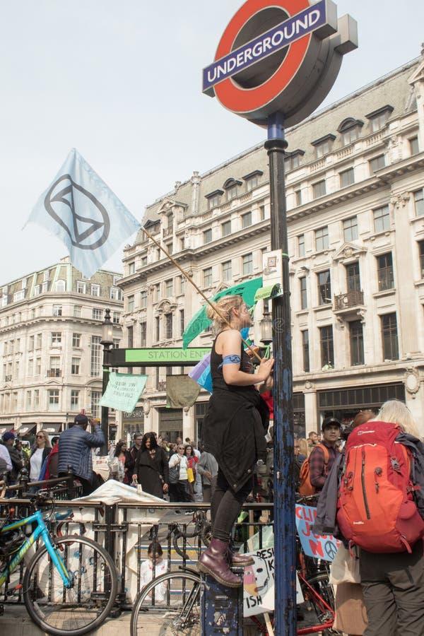 London UK, April 17 2019 - unga kvinnliga klimatförändringperson som protesterarvågor en utplåningrevoltflagga utanför Oxford Cir arkivfoto
