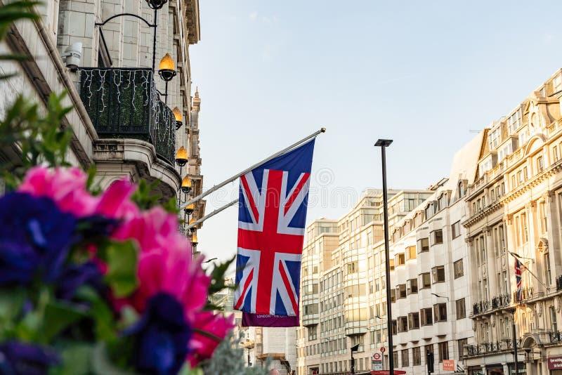 LONDON UK - APRIL 1, 2019: Union Jack Flag på en storgata i London arkivbild