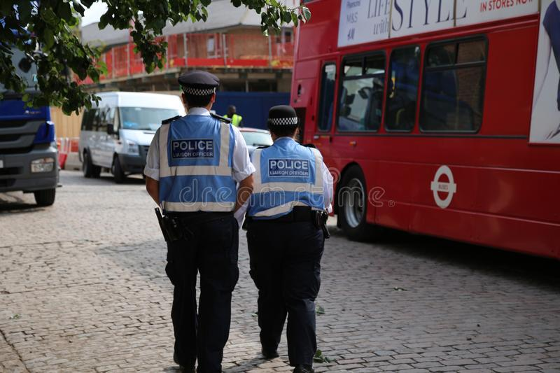 British police officers with high visable blue jackets patrolling royalty free stock photography