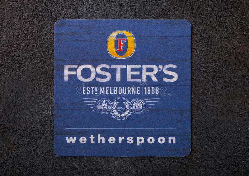 LONDON, UK - AUGUST 22, 2018: Foster`s beer beermat coaster on black background. LONDON, UK - AUGUST 22, 2018: Foster`s paper beer beermat coaster on black royalty free stock images