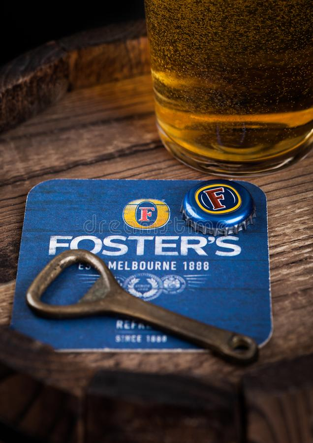 LONDON, UK - AUGUST 10, 2018: Foster`s beer coaster with bottle top and opener and glass of beer on top of wooden barrel. royalty free stock photography