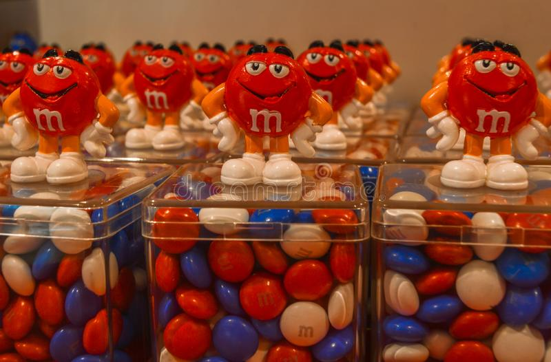 London, UK - August 7, 2018: M&M`s colorful chocolate candies in plastic containers, with red character mascot on top royalty free stock images